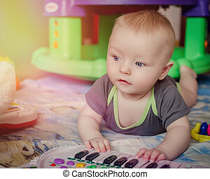 Baby boy playing with piano toy - Portrait of little baby...