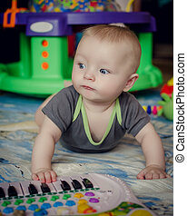 Baby boy playing with piano toy - Happy little baby boy...