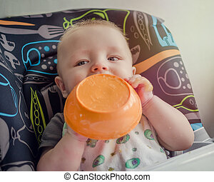 Adorable baby learning to feed himself for the first time -...