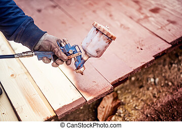 construction worker painting with spray gun