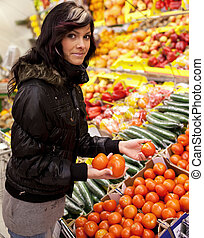 Beautiful young woman shfruits and vegetables at a supermarket/grocery