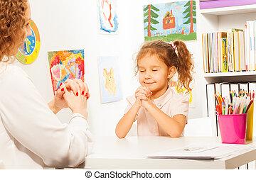 Schoolgirl exercises putting fingers with teacher -...