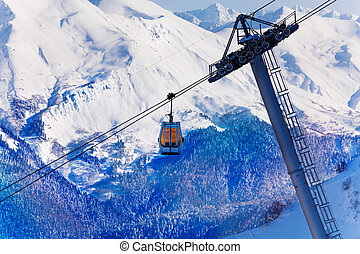 Lonely cable car cabin over snow peaks
