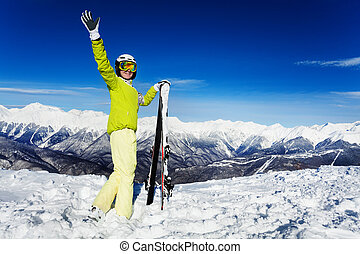 Waving skier woman portrait over mountain peaks - Full...
