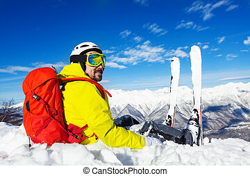 Skier with backpack sit on top of the mountain