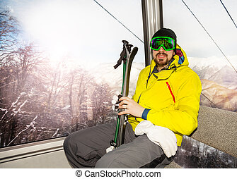 Man skier sit in ski lift cable car cabin - Man skier with...