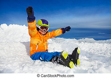 Happy skier boy sit with lifted hands in snow - Little boy...