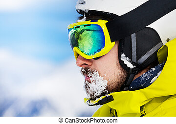 Portrait of man in ski googles and snow on beard - Close...