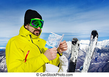 Man with map of ski pistes over the mountain peaks - Man on...
