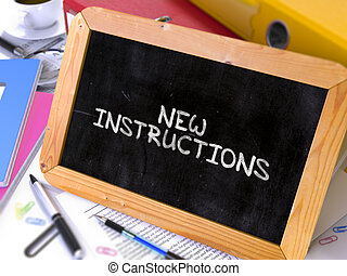 New Instructions Handwritten by White Chalk on a Blackboard...