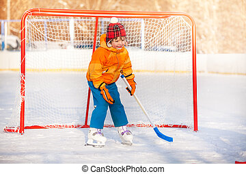 Little boy goalkeeper play ice hockey