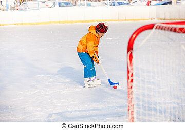 Little boy play ice hockey outside