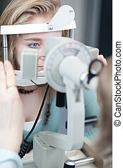 optometry concept - pretty young woman having her eyes...