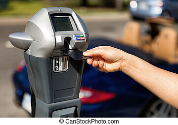 Hand putting credit card into parking meter with convertible...