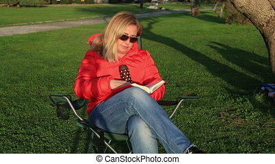 Woman reading and relaxing in park - Middle age, blonde...