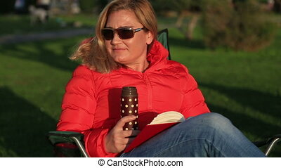 Woman relaxing in the park - Middle age, blonde woman...