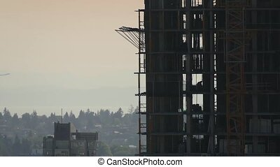 Plane Passes Construction Building - Plane flies past a...