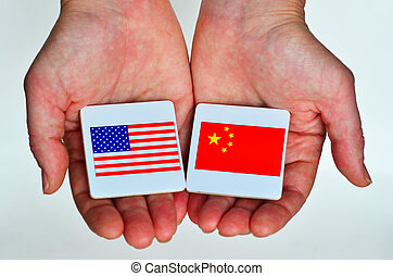 Two hands holds the national flags of the United States of...