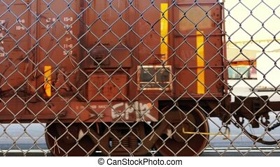 Train Passing Behind Chain Fence - Large train boxcars...