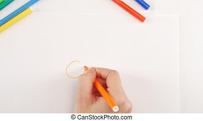 Woman drawing the sun using yellow felt-tip pen on white...