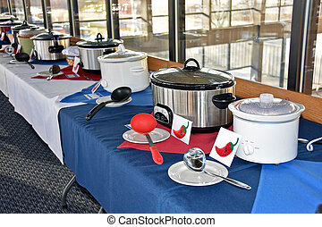 chili cook off - Row of crock pots with ladles for chili...