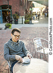 Young asian man in outdoor cafe - Young asian man sitting...