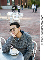 Young asian man in outdoor cafe with cup of coffee looking...
