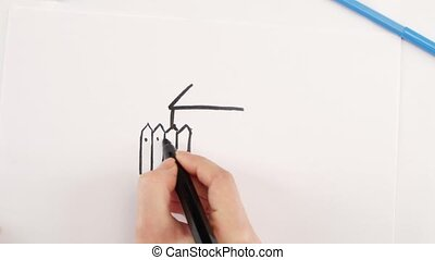 Woman drawing the house using black felt-tip pen on white...