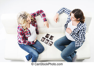 Two attractive pregnant women watching ultrasound photos