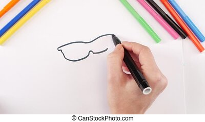 Woman drawing the glasses using black felt-tip pen on white...