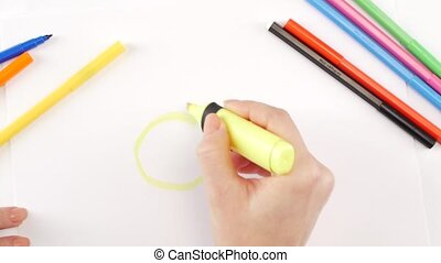 Woman drawing the pear using yellow felt-tip pen on white...