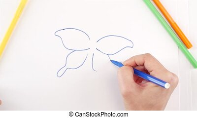 Woman drawing the butterfly using different felt-tip pen on...