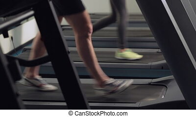A man and a girl go on the treadmil