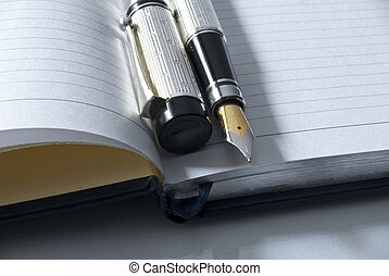 fountain pen & diary - fountain pen on a blank diary over a...