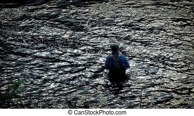 Angler Fishing Waist-Deep In River - Fisherman casts his...