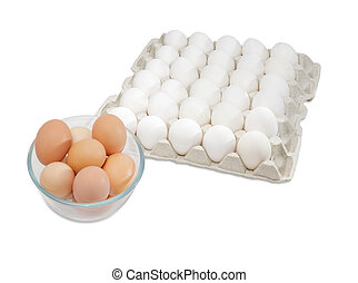 White eggs in egg tray, brown eggs in glass bowl