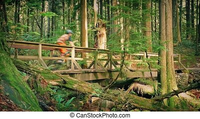 Cyclists Ride Over Wooden Bridge