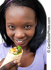 Charming young woman eating a wrap against a white...