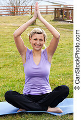 Jolly woman doing yoga sitting on the grass in a park