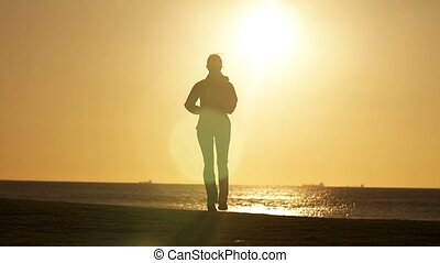 woman jogging isolated in park by beach early morning exercise slowmo