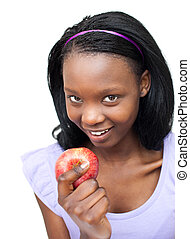 Delighted afro-american woman eating an apple against a...