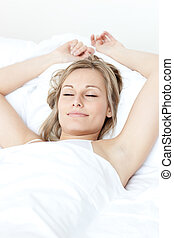 Relaxed woman sleeping on a bed against a white background