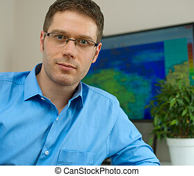 Handsome male meteorologist in glasses on his workplace