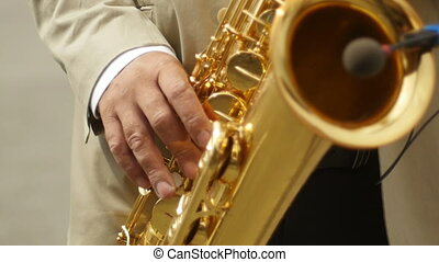 playing saxophone sunlight - Panning shot of musician...