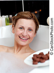 Radiant woman eating chocolate while having a bath in a spa...