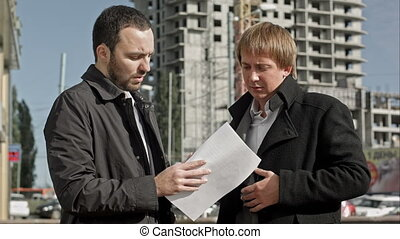Contractor and investor discussing housing project....