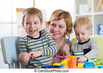 Family molded from clay toys. Mother play with children.
