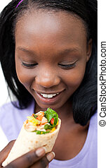 Delighted woman eating a wrap