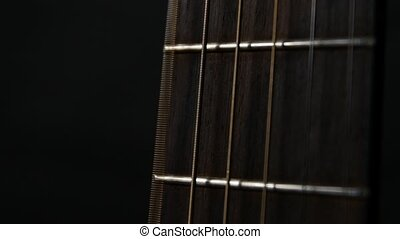 Acoustic guitar strings, close up, slow motion, on black...