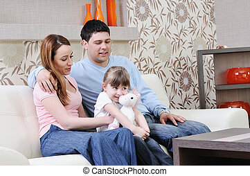 happy young family at home - happy youg family relaxing in...